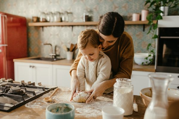 Young mother and little son are making dough for cookies together. They are happy and mother is overseeing him. They wear casual winter clothes.