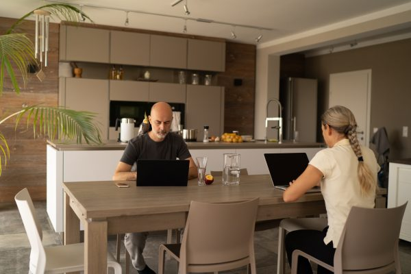 Couple working from home on kitchen table during coronavirus pandemic