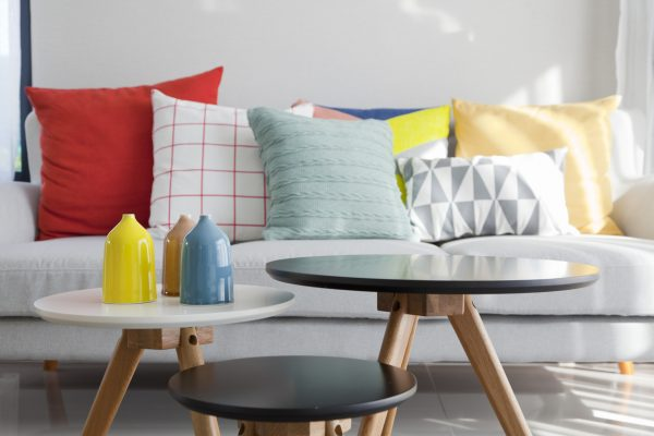 Grey sofa with many colorful pillows on it in livingroom